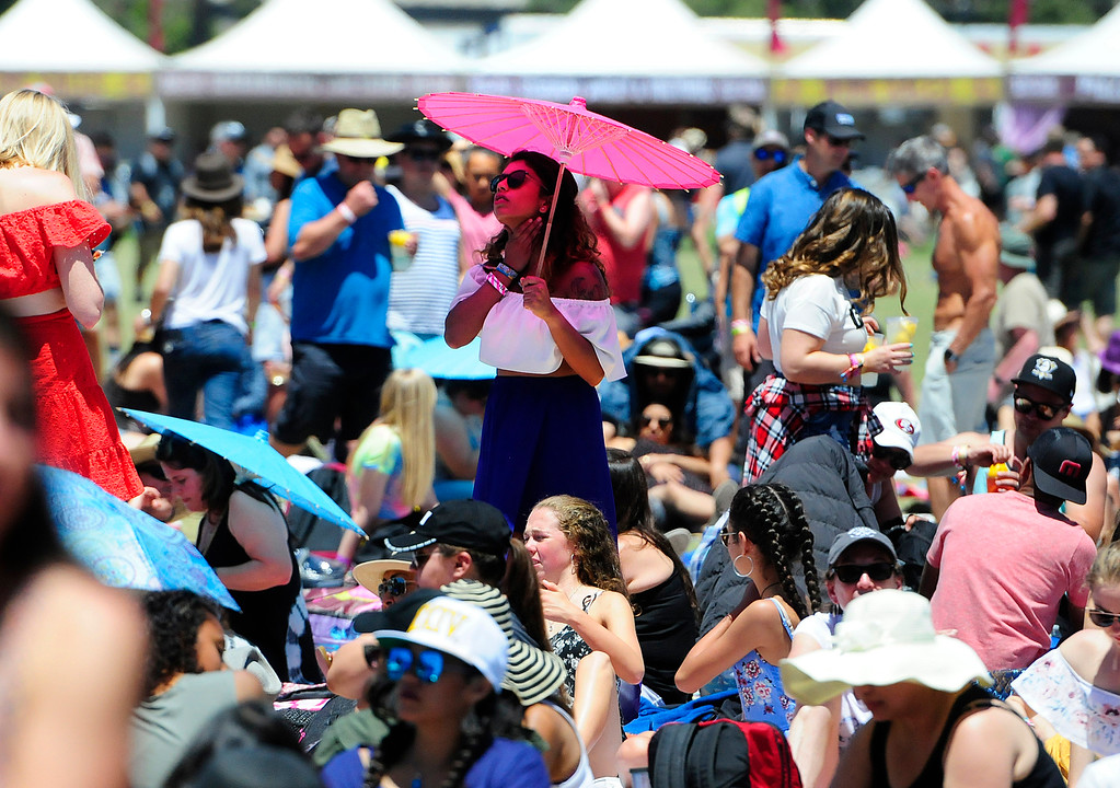 . NAPA, CA - MAY 27, A Bottlerocker beats the heat under the shade of an umbrella as she waits for bands to go on at the Jam Cellars Stage on Sunday, on the last day of the BottleRock Napa Valley Music Festival. (CHRIS RILEY/TIMES-HERALD)
