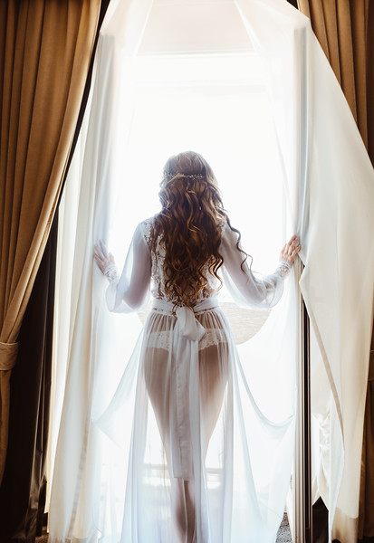 Silhouette of sexy young brunette woman in white lingerie in the doorway opening curtains