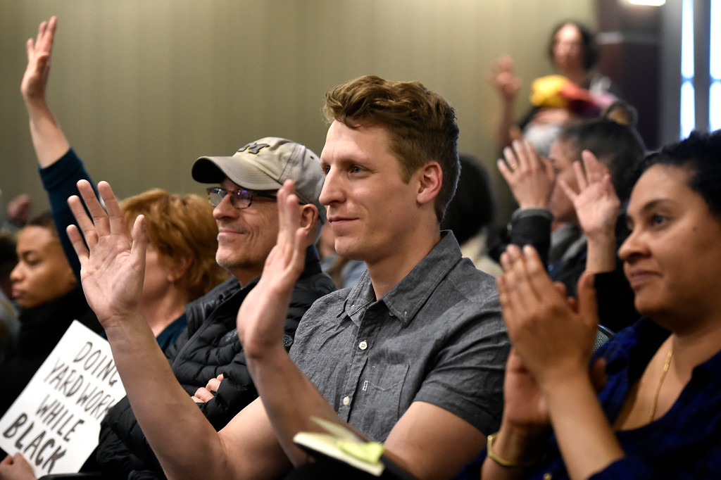 . BOULDER, CO - MARCH 18, 2019: Adam Swetlik, of Boulder, at center, holds his hands up as he agrees with a community members speech during a special Boulder City Council meeting on Monday night regarding the recent incident of racial profiling. For more photos of the meeting go to dailycamera.com (Photo by Jeremy Papasso/Staff Photographer)