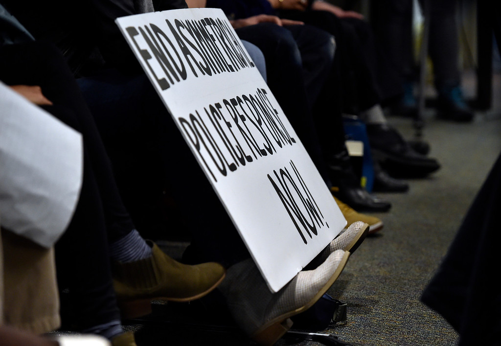 . BOULDER, CO - MARCH 18, 2019: A woman rests a sign on her feet during a special Boulder City Council meeting on Monday night regarding the recent incident of racial profiling. For more photos of the meeting go to dailycamera.com (Photo by Jeremy Papasso/Staff Photographer)