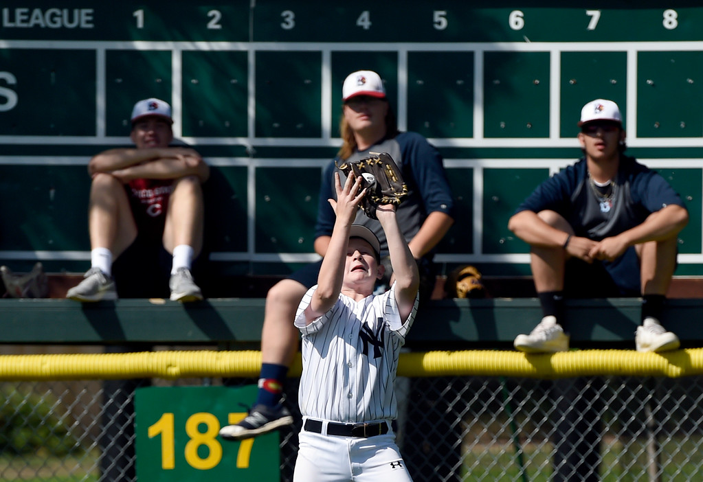 . Sean Williams, 11, makes a catch in center field under the watch of Boulder Collegians players during a Boulder Collegians Youth Camp at the Iris Ballfields in Boulder on Tuesday. For more photos of the youth baseball camp go to dailycamera.com Jeremy Papasso/ Staff Photographer 06/12/2018