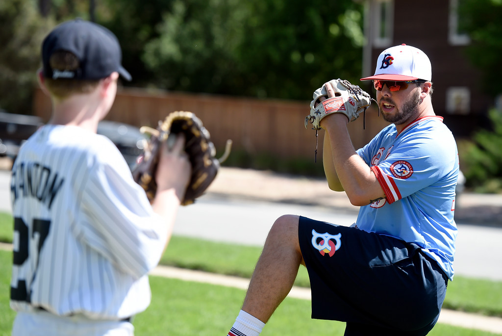 . Boulder Collegians pitcher Roger Kruse demonstrates pitching technique to Sean Williams, 11, during a Boulder Collegians Youth Camp at the Iris Ballfields in Boulder on Tuesday. For more photos of the youth baseball camp go to dailycamera.com Jeremy Papasso/ Staff Photographer 06/12/2018