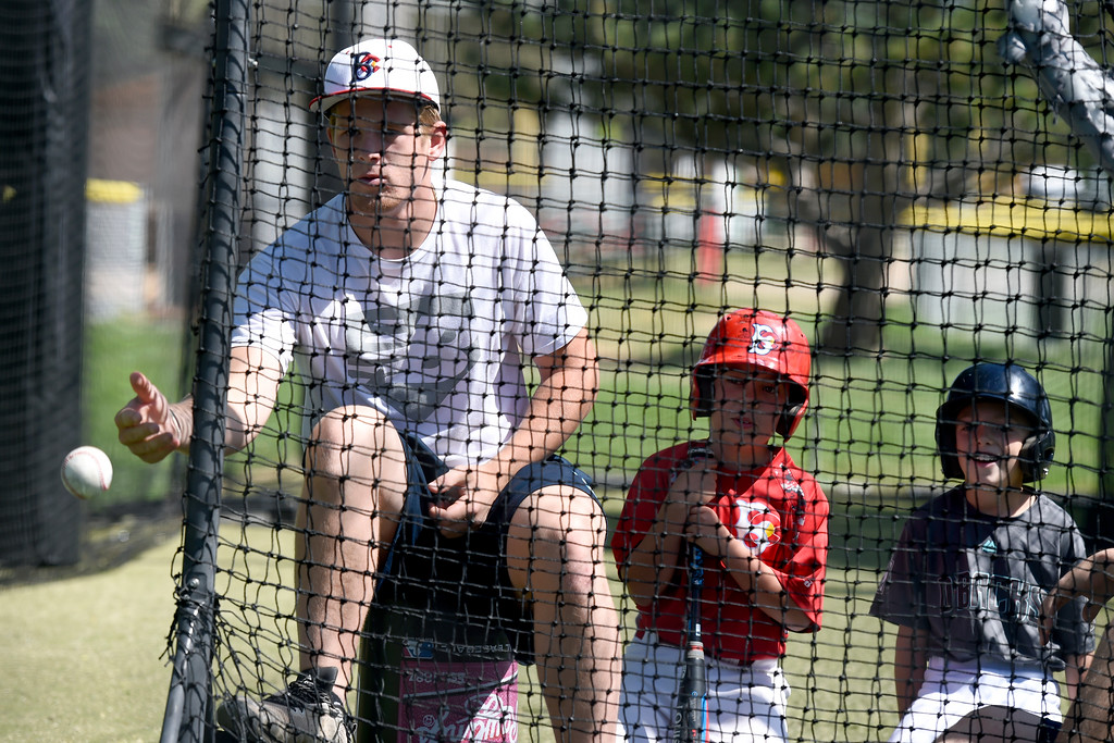 . Boulder Collegians catcher Brett Bonar throws a ball to a little league player during batting practice during a Boulder Collegians Youth Camp at the Iris Ballfields in Boulder on Tuesday. For more photos of the youth baseball camp go to dailycamera.com Jeremy Papasso/ Staff Photographer 06/12/2018