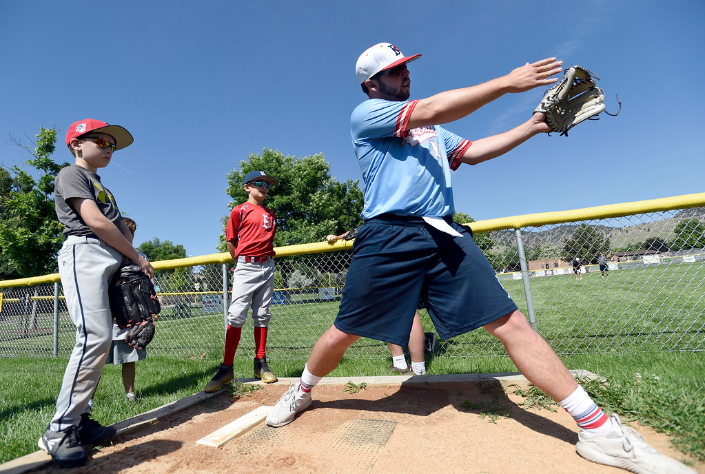 . Boulder Collegians pitcher Roger Kruse demonstrates pitching technique to a group of little league players including Owen Lipinski, 9, left, and Brody Simpson, 9, during a Boulder Collegians Youth Camp at the Iris Ballfields in Boulder on Tuesday. For more photos of the youth baseball camp go to dailycamera.com Jeremy Papasso/ Staff Photographer 06/12/2018