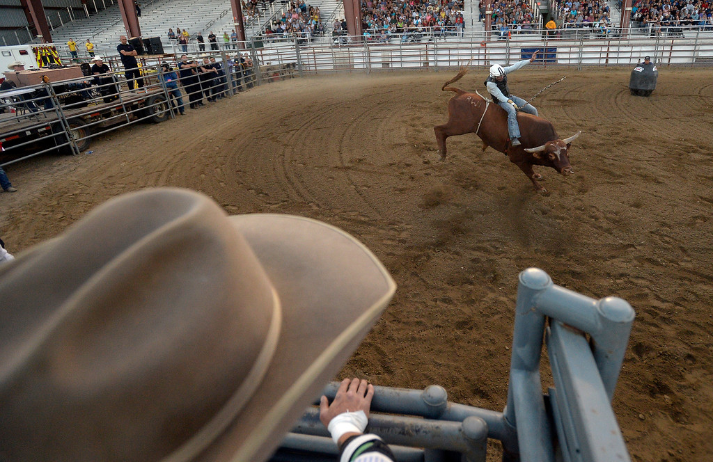 . A bullrider hangs on during the Boulder County Fair on Friday night at the Boulder County Fairgrounds in Longmont. For more photos of the rodeo go to dailycamera.com Jeremy Papasso/ Staff Photographer 08/10/2018