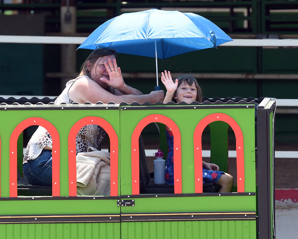 . Cheryl Bonham, left, and her granddaughter, Lua, wave to friends while riding the train during the Boulder County Fair in Longmont on Tuesday, August 7, 2018. For more photos, go to dailycamera.com. Cliff Grassmick  Staff Photographer  August 7, 2018