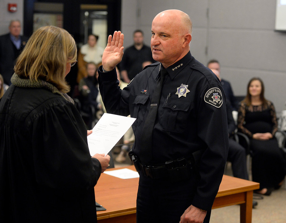 . BOULDER, CO - January 8, 2019: Boulder County Sheriff, Joe Pelle, is being sworn in by Judge Ingrid Bakke.  Boulder County  officials took their oaths of office on Tuesday January 8, 2019 at the Boulder County Courthouse. (Photo by Cliff Grassmick/Staff Photographer)