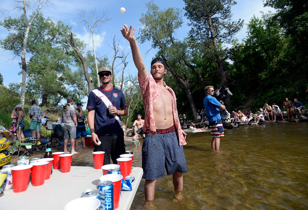 . Scott Reba, right, and Nate Widhalm play a game of beer pong while hanging out at the Boulder Creek on Wednesday, in Boulder. For more photos of the overcrowded Boulder Creek go to dailycamera.com Jeremy Papasso/ Staff Photographer 07/04/2018