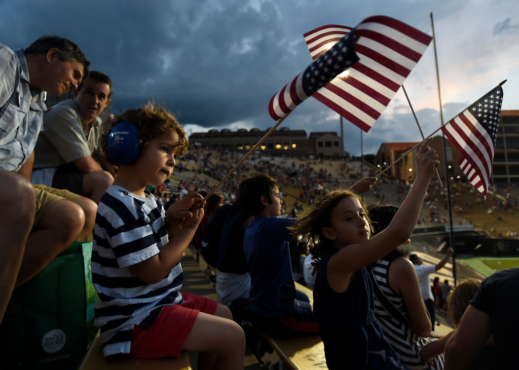 . Azlan Makovec, 4, left, and Nora Iturpe, 7, wave American flags before the start of the Ralphie\'s Independence Day Blast at Folsom Field on the University of Colorado campus in Boulder. For more photos of the event go to dailycamera.com Jeremy Papasso/ Staff Photographer 07/04/2018