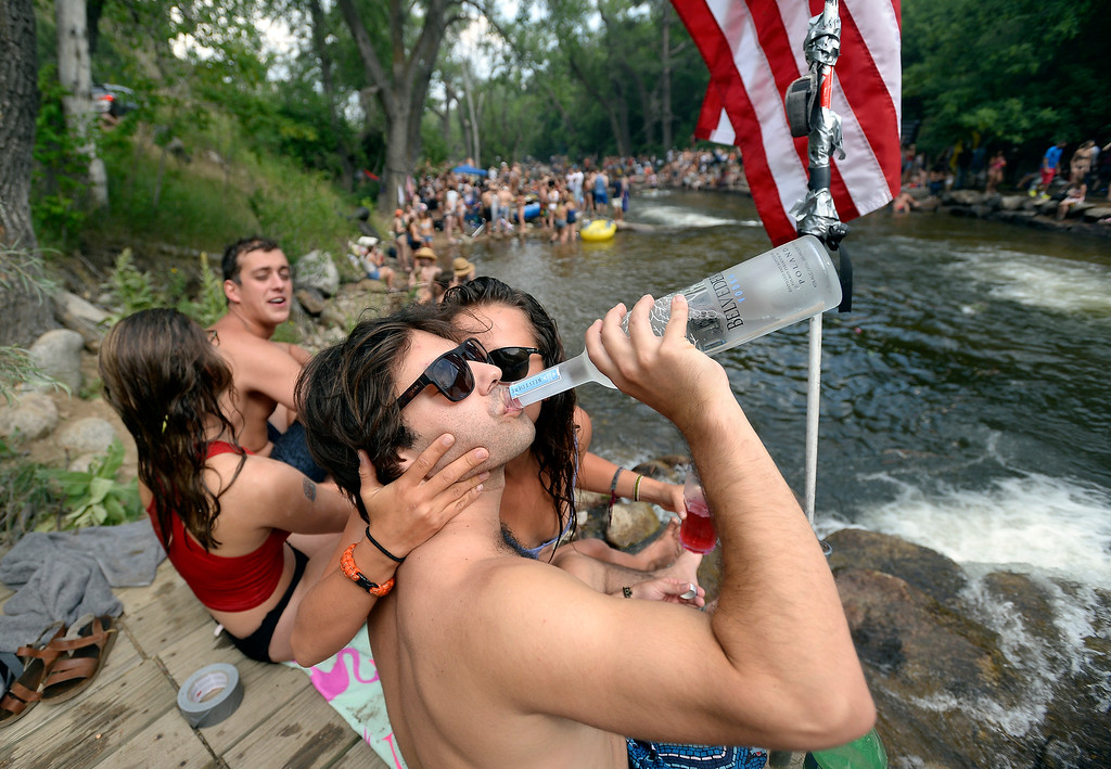 . Jason Egelanian, of Boulder, takes a drink from a vodka bottle and gets a kiss from Natalie Taja while hanging out at the Boulder Creek on Wednesday, in Boulder. For more photos of the overcrowded Boulder Creek go to dailycamera.com Jeremy Papasso/ Staff Photographer 07/04/2018