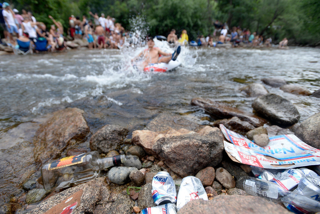 . A tuber floats past a pile of empty alcohol bottles and cans at the Boulder Creek on Wednesday, in Boulder. For more photos of the overcrowded Boulder Creek go to dailycamera.com Jeremy Papasso/ Staff Photographer 07/04/2018