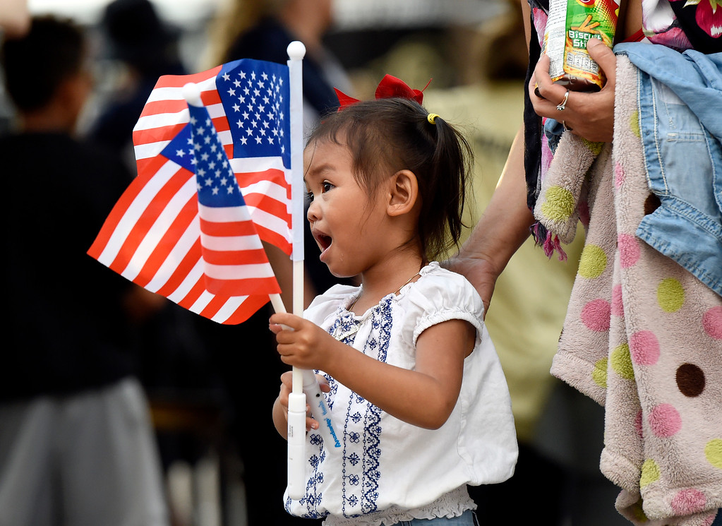 . Camellia Altanochir waves two American flags while waiting in line for the Ralphie\'s Independence Day Blast at Folsom Field on the University of Colorado campus in Boulder. For more photos of the event go to dailycamera.com Jeremy Papasso/ Staff Photographer 07/04/2018