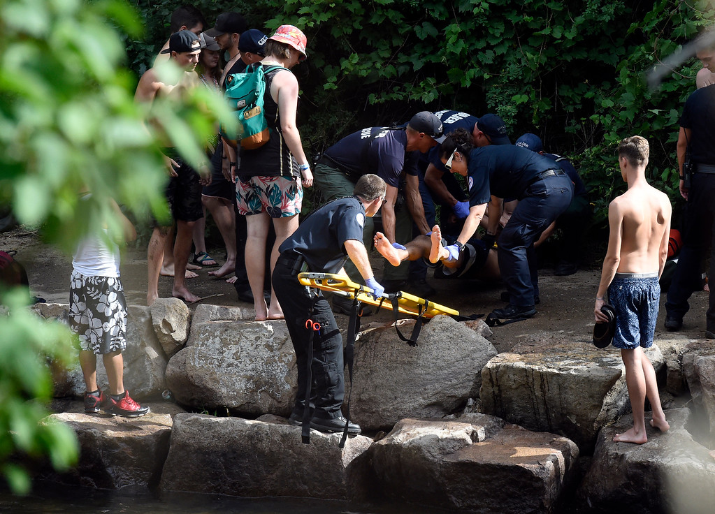. A man is taken off in a stretcher by paramedics after allegedly hitting his head on a rock at the Boulder Creek on Wednesday, in Boulder. For more photos of the overcrowded Boulder Creek go to dailycamera.com Jeremy Papasso/ Staff Photographer 07/04/2018