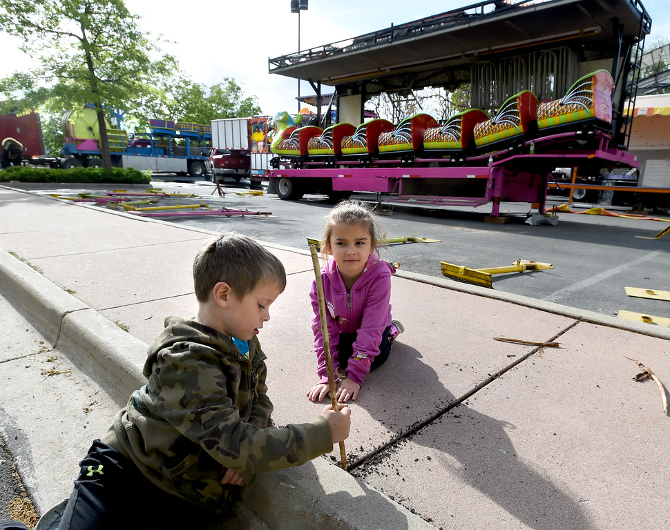 . Raidynn Moore, left, and his cousin, Xiumara Burgos, both 5, play near the carnival that their family owns. Staff from Gary Moore Amusements are putting together the carnival rides along Boulder Creek Friday morning. For more photos, go to www.dailycamera.com.  Cliff Grassmick  Staff Photographer May 26, 2017