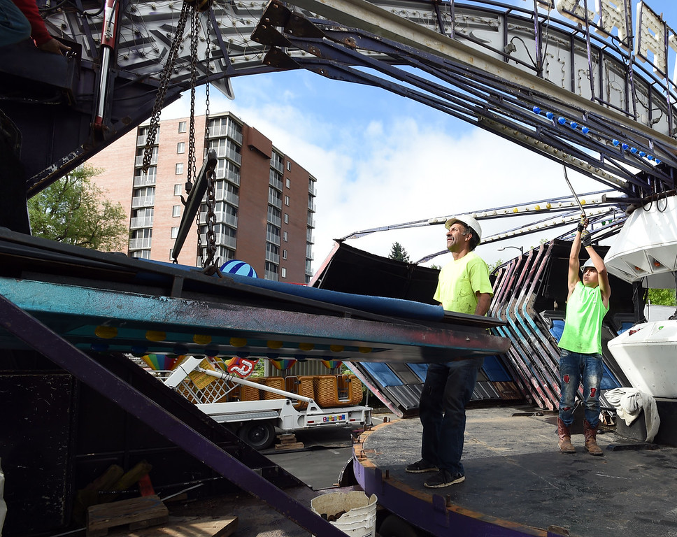 ". Austin Lumbreras, right, works with ""Luigi\""  to put together the \""StarZhip 3000\""  on Friday morning. Staff from Gary Moore Amusements are putting together the carnival rides along Boulder Creek. For more photos, go to www.dailycamera.com.  Cliff Grassmick  Staff Photographer May 26, 2017"