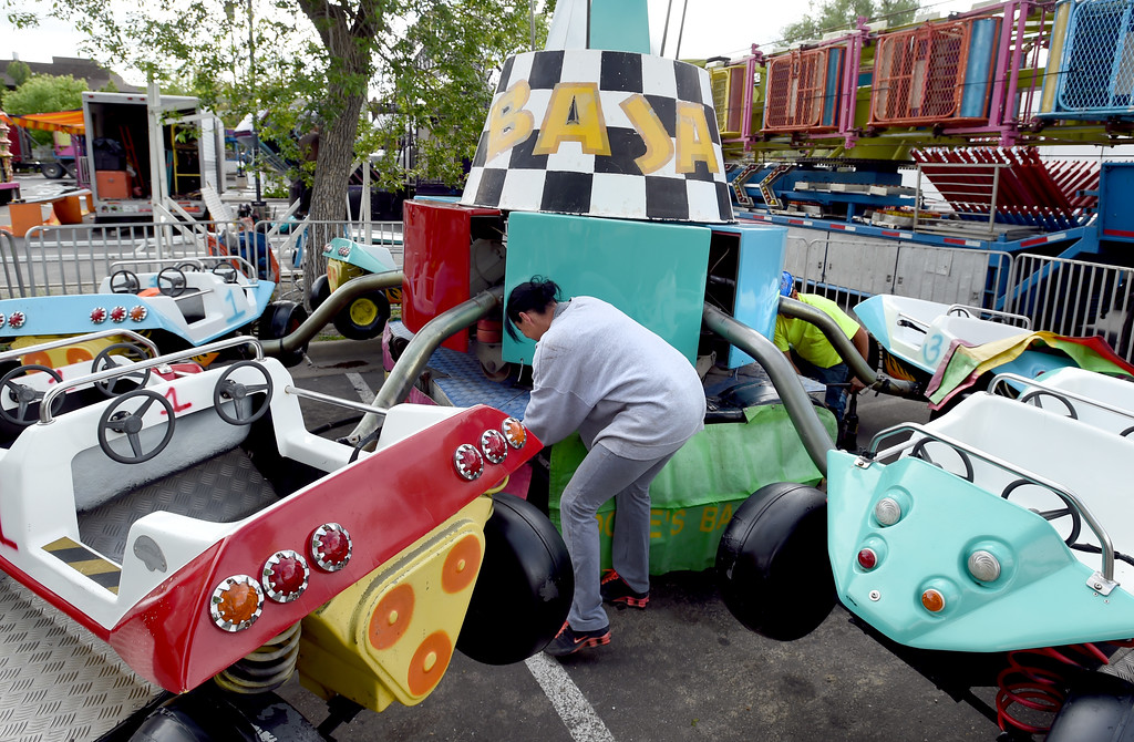 . Debra Tate helps put together one of the rides. Staff from Gary Moore Amusements are putting together the carnival rides along Boulder Creek Friday morning. For more photos, go to www.dailycamera.com.  Cliff Grassmick  Staff Photographer May 26, 2017