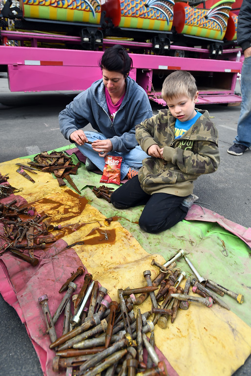. Danielle Moore and Raidynn Moore, 5, clean and sort bolts.  Staff from Gary Moore Amusements are putting together the carnival rides along Boulder Creek Friday morning. For more photos, go to www.dailycamera.com.  Cliff Grassmick  Staff Photographer May 26, 2017