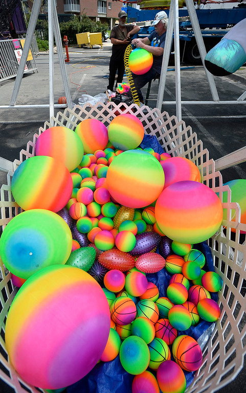. Robert Stevens blows up colorful balls for the arcade games. Staff from Gary Moore Amusements are putting together the carnival rides along Boulder Creek Friday morning. For more photos, go to www.dailycamera.com.  Cliff Grassmick  Staff Photographer May 26, 2017