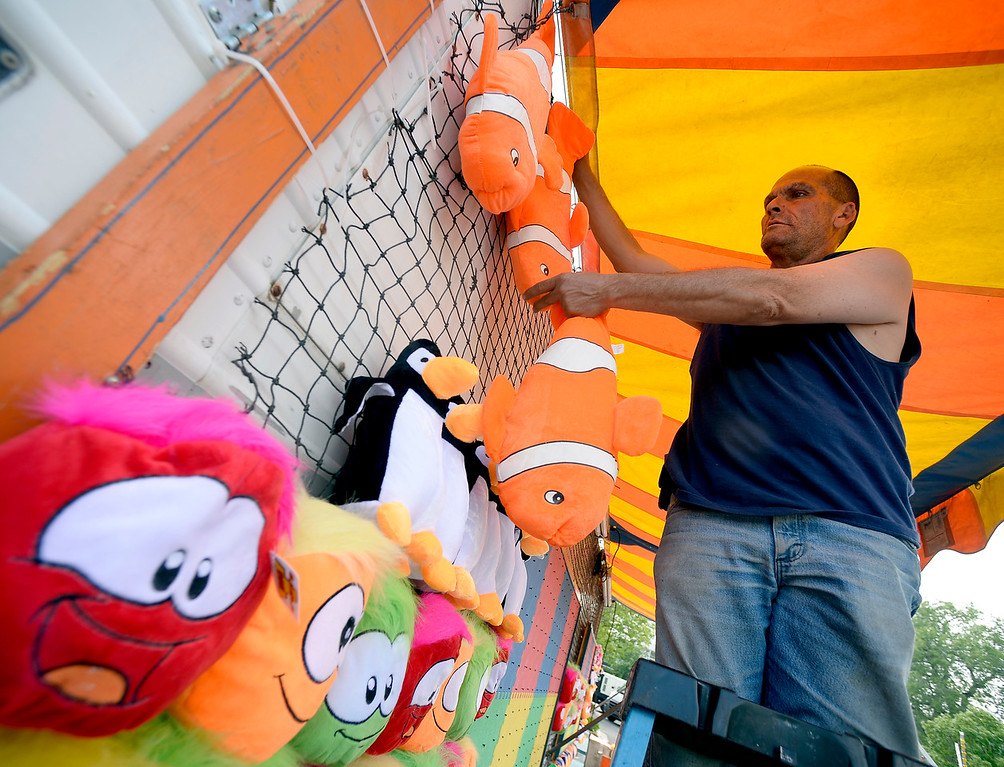 . A carnival worker hangs up stuffed animals for the arcade games. Staff from Gary Moore Amusements are putting together the carnival rides along Boulder Creek Friday morning. For more photos, go to www.dailycamera.com.  Cliff Grassmick  Staff Photographer May 26, 2017