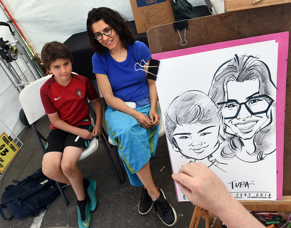 . Ali Holt, left, and his mother, Tuba Ustuner, become a work of art by Chad Straka at the festival on Saturday. The Boulder Creek Festival is free to the public and and has  9 separate event areas with 500 vendors showcase everything from community arts and crafts to healthier alternatives and technology while 3 performance stages feature a spectrum of music and dance.  The festival also features carnival rides and food and beverage vendors. The festival continues through Monday. For for more photos, go to dailycamera.com. Cliff Grassmick  Photographer  May 26,  2018