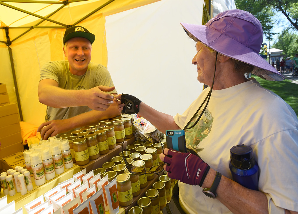. Bjorn Jakobsson, left, gives a sample of his honey to Rose Brainerd at the creek festival on Saturday. The Boulder Creek Festival is free to the public and and has  9 separate event areas with 500 vendors showcase everything from community arts and crafts to healthier alternatives and technology while 3 performance stages feature a spectrum of music and dance.  The festival also features carnival rides and food and beverage vendors. The festival continues through Monday. For for more photos, go to dailycamera.com. Cliff Grassmick  Photographer  May 26,  2018