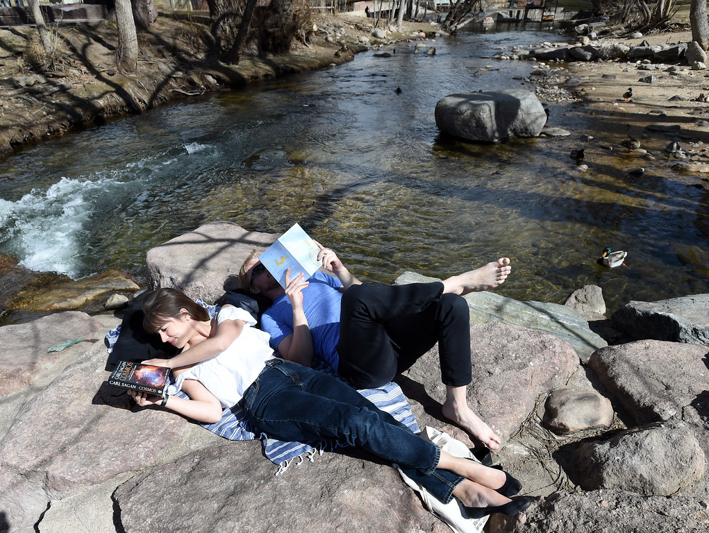 . University of Colorado graduate students,  Valeria Serrano and Jake Mashburn,  relax and read on rocks in Boulder Creek. Several people were enjoying Boulder Creek near the Boulder Public Library on Friday. For more photos, go to dailycamera.com. Cliff Grassmick  Photographer  March 9, 2018
