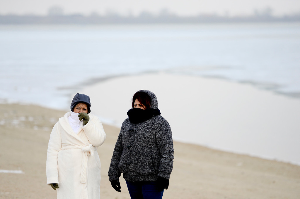 . From left: Maria Contreras and Maria Cordova, both of Lafayette, wait for the start of the Boulder Polar Plunge while trying to stay warm at Boulder Reservoir in Boulder, Colorado on Jan. 1, 2018. (Photo by Matthew Jonas/Times-Call)