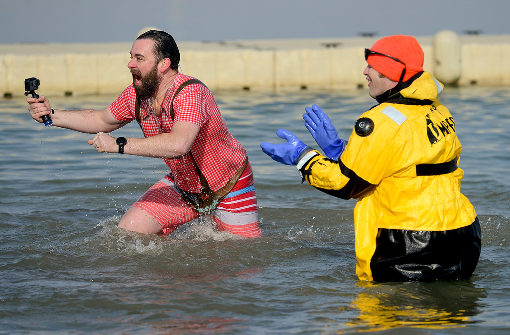 . A participant emerges from the water during the Boulder Polar Plunge, a benefit for the American Cancer Society, at Boulder Reservoir in Boulder, Colorado on Jan. 1, 2018. (Photo by Matthew Jonas/Times-Call)