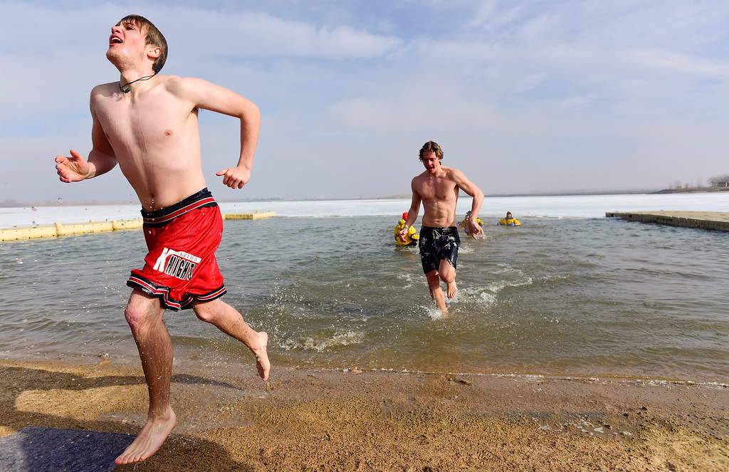 . Participants emerge from the water during the Boulder Polar Plunge, a benefit for the American Cancer Society, at Boulder Reservoir in Boulder, Colorado on Jan. 1, 2018. (Photo by Matthew Jonas/Times-Call)