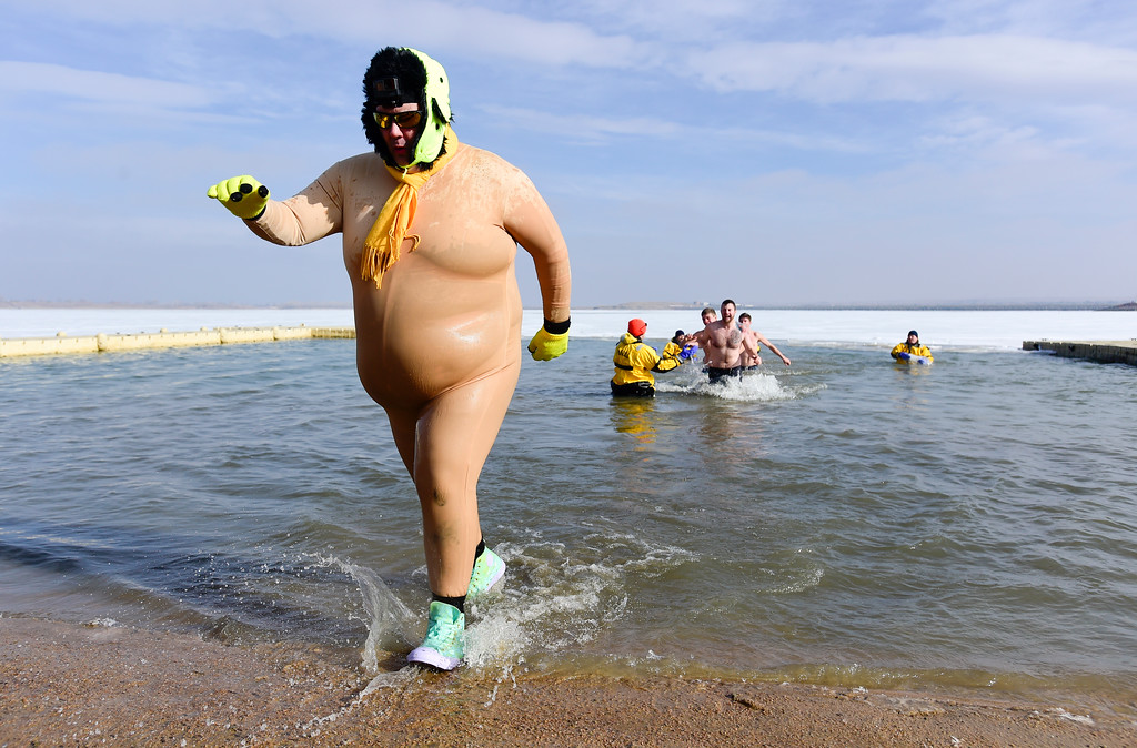 ". James ""Booboo\"" Wilde, of Boulder, emerges from the water during the Boulder Polar Plunge, a benefit for the American Cancer Society, at Boulder Reservoir in Boulder, Colorado on Jan. 1, 2018. (Photo by Matthew Jonas/Times-Call)"