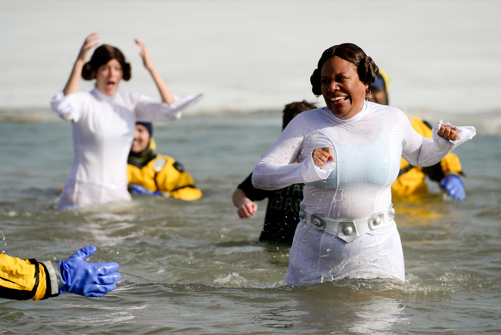 ". From left: ""Don\'t call me Princess!\"" team members Michelle Kinkead, Patrick Maring and Carol Banks Bane react as they make their way out of the water during the Boulder Polar Plunge, a benefit for the American Cancer Society, at Boulder Reservoir in Boulder, Colorado on Jan. 1, 2018. (Photo by Matthew Jonas/Times-Call)"