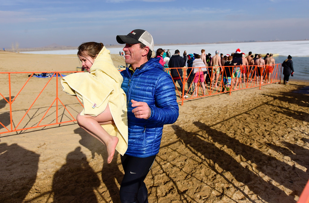 . Simon Sparks carries his daughter Ruby Sparks, 4, both of Boulder, after she jumped into the water during the Boulder Polar Plunge, a benefit for the American Cancer Society, at Boulder Reservoir in Boulder, Colorado on Jan. 1, 2018. (Photo by Matthew Jonas/Times-Call)