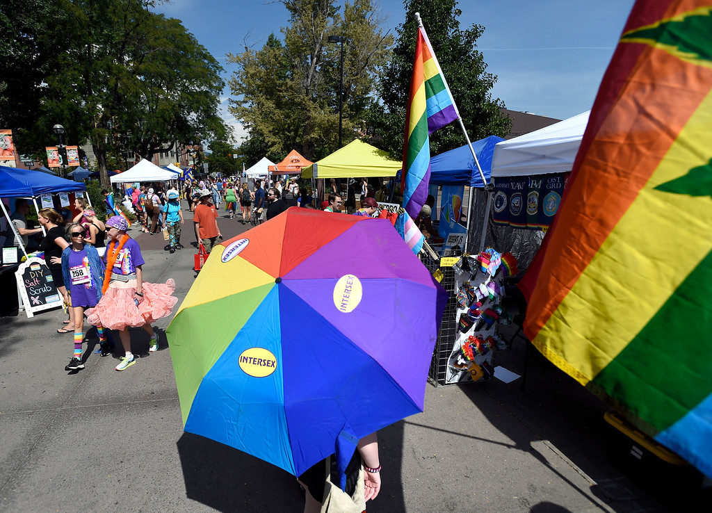 . Ace Noland carries a rainbow colored umbrella while walking through the vendor area during the Boulder Pridefest 2017 celebration on Sunday at Central Park in Boulder, Colo. For more photos of the Pridefest celebration go to dailycamera.com Jeremy Papasso/ Staff Photographer/ Sept. 10, 2017