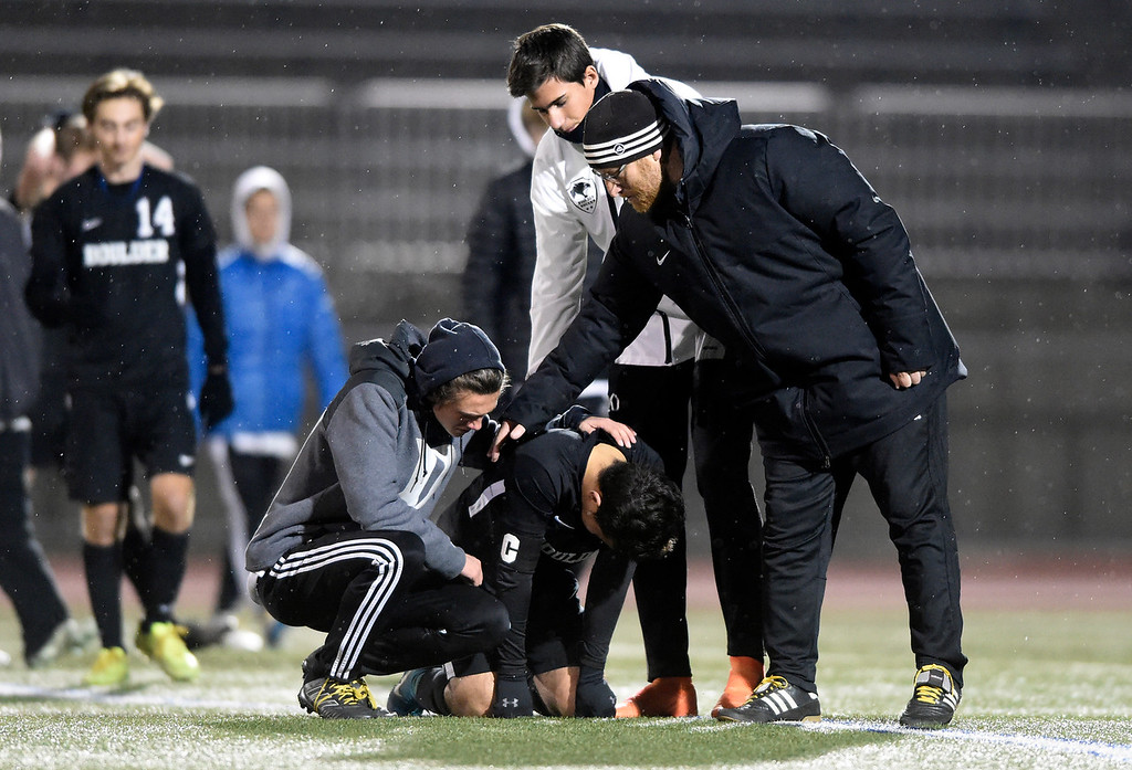 . PARKER, CO - NOVEMBER 7, 2018: Boulder High School\'s Omar Castruita is consoled by teammates and Head Coach Hardy Kalisher after losing a CHSAA 5A semi-final playoff game against Grandview High School on Wednesday at Echo Park Stadium in Parker. Boulder lost the game 2-0. More photos: BoCoPreps.com