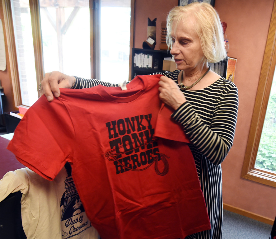 . Nikki Kayser shows one of the many t-shirts available at KGNU. Boulder\'s KGNU community radio station is turning 40 this year and is hosting some events throughout the year to commemorate. For more photos, go to dailycamera.com. Cliff Grassmick  Photographer  May 9,  2018