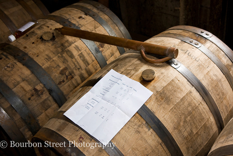 Sampling the barrels.  The copper 'whiskey thief' is used to draw out a sample for tasting.