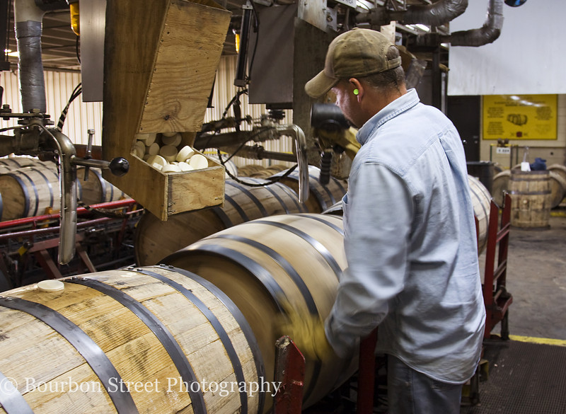 Barrel filling station.  The worker is spinning the barrel to bring the bung hole to the top.  <br /> <br /> The barrel is filled with whiskey and then sealed with a poplar bung.  (I did get to seal one myself)  <br /> <br /> The full barrels weigh about 500lbs and are carried away on a conveyer to be loaded in a truck.