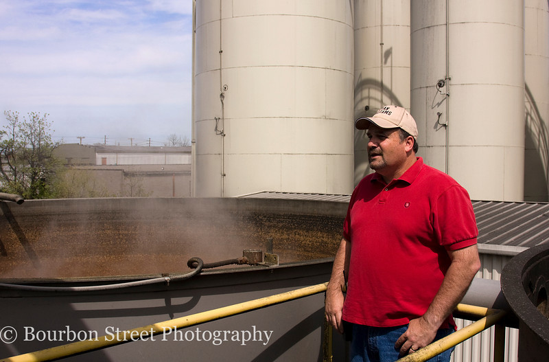 "Shift Supervisor Tony Skaggs shows off the large ""slop"" tanks.  <br /> <br /> Slop is the spent distillers beer that has had the alcohol stripped from it by distillation. Heaven Hill gives it away to local farmers as a high protein animal feed.  <br /> <br /> Grain silos in the background."