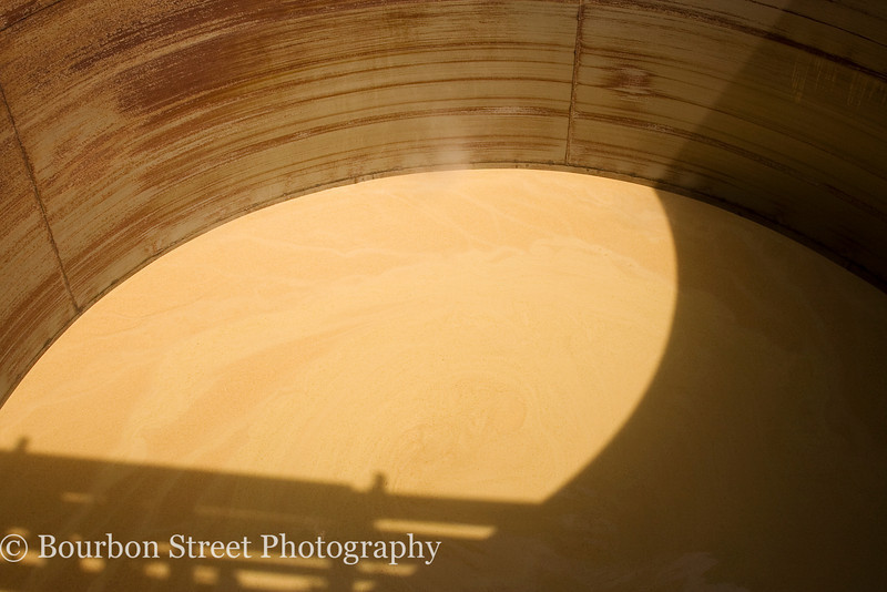 "Peering into a ""slop"" tank.  The thick liquid is the by-product of whiskey distillation and is used as animal feed."