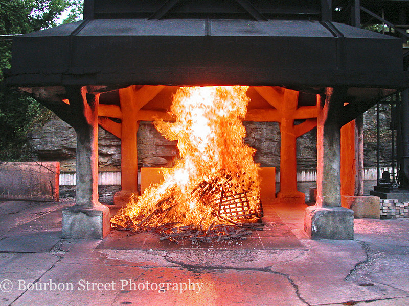 The Rickyard. <br /> <br /> It takes 2-3 hours to burn a rick of maple into the charcoal used to filter Jack Daniels Tennessee Whiskey and give it some of its unique flavor.  <br /> <br /> The wood is ignited with a splash of 135-proof whiskey.