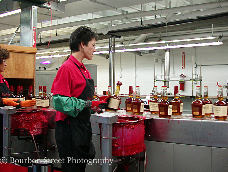 The bottling house is particularly interesting. <br /> <br /> Four workers hand dip the bottles in the trade mark red plastic goo as they pass on the conveyor belt. The line moves at a good clip, and the 'dippers' have to have the process down cold. <br /> <br /> The workers rotate between stations at frequent intervals for a change of pace and to help prevent repetitive motion strain.