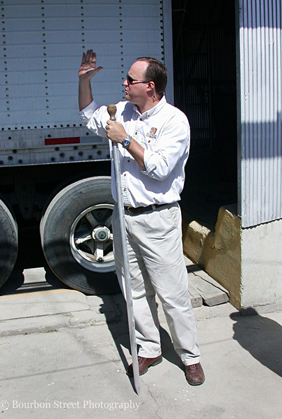 Master Distiller Greg Davis.  The long pole Greg is holding, called a grain thief, is used to take samples from a delivery truck for testing.