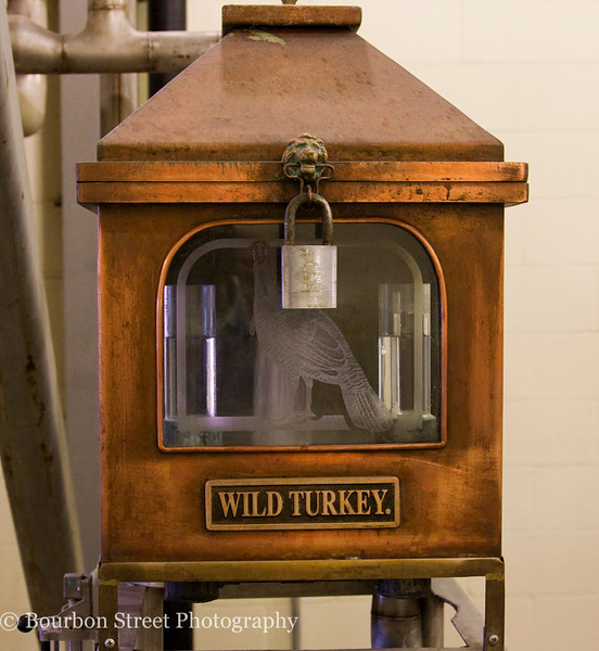 The 'low wines' spirit safe.  This ornate equipment is traditional in the whiskey industry.  The distiller can open this box to take a sample of the spirit coming off the still to check for quality.  Notice the turkey engraved into the glass and the lion's head on the latch.