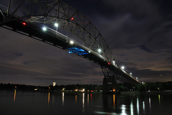 The Bourne Bridge, in all its elegance, glistens in the late August night sky. The three red streaks you see on the lower left and middle of this picture are airplanes. The streaks are caused by the extended length of the exposure.