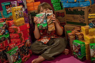 """REDONDO BEACH , CALIFORNIA — William poses with the 110 Girl Scout cookie boxes Annette sold in her first year as a Brownie. The """"studio"""" was in the Sorensen living room. Photo by Tom Sorensen Saturday February 28th, 2009."""