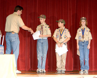 Kevin, Minh, and Teddy receive special recognition for completing all Activity Badges in the Cub Scout program.