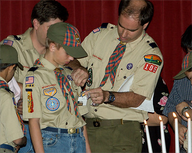 Den leader and past Cub Master Pete pins on son Kevin's award.