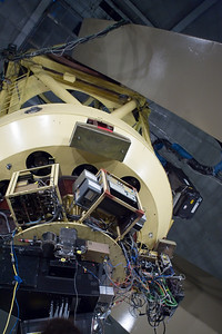 "In this view, looking up at the 120-inch reflector from below, we see one arm of the giant ""fork"" that holds it, and, on the right side, the powerful laser used to generate the ""artificial star"" for the cutting-edge adaptive optics technology."