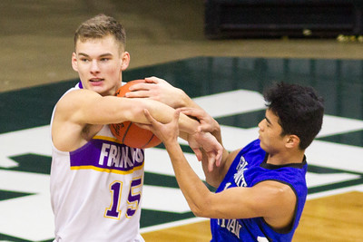 Record-Eagle/Brett A. Sommers Frankfort's Conner Smith gets tangled up with a Tri-unity Christian defender during Thursday's Division 4 state semifinal boys basketball game at the Breslin Center in East Lansing.