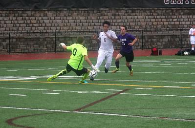Ellington goalkeeper Zachary Mozzer holds off a rush from Canton's Jesse Waite.